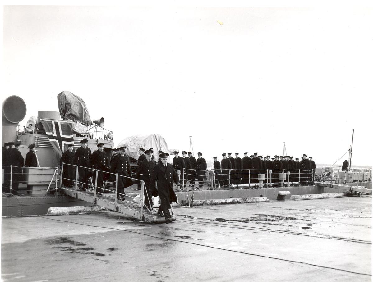 """Overtakelsen av River-kl.fregatt KNM """"Draug"""", ex. HMCS Pentang 25. januar 1956. Det kanadiske mannskapet går i land etter at kommandoen er strøket på HMCS Pentang."""
