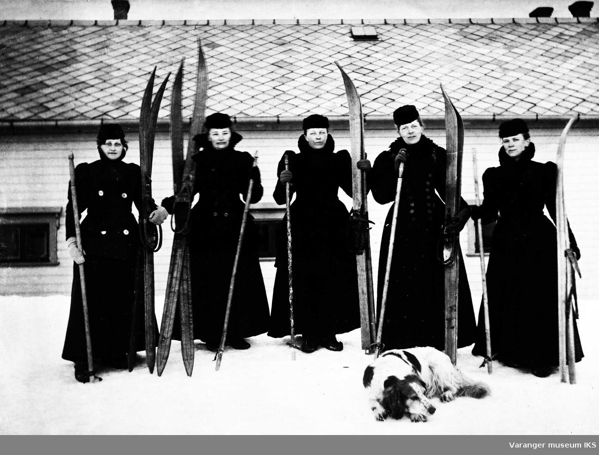 5 damer med ski og hund foran Amtmannsgården 1898. Frk Bentserud, fru skolebestyrer Agnes Elise Schønheyder, fru sorenskriver Randers, fru amtmann Minka Graff og fru apoteker Bolette Berentzen.