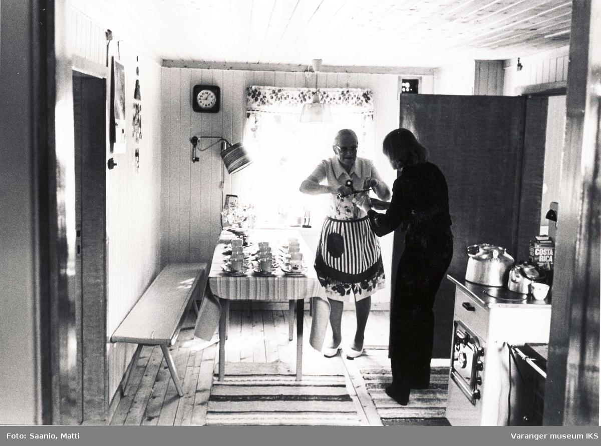 Ida Tuomainen på kjøkkenet i Tuomainengården med en annen dame. 1977