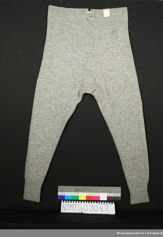 Lange ben. Innside av bærestykke av innfelt lin. Framside: Påsydde bånd og åpning med 3 knapper. Baksiden: Åpning med justerbart bånd.