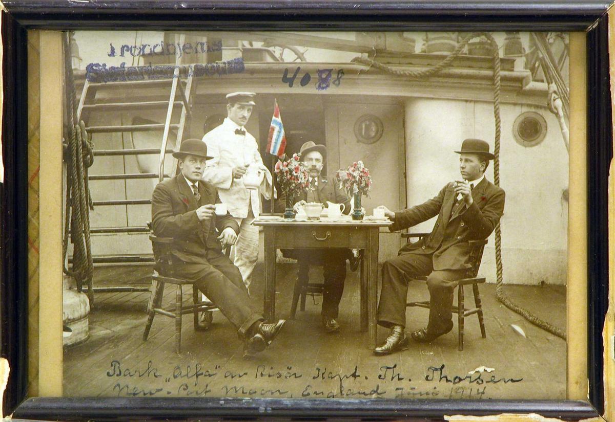 """Kapteinen, 1. og 2. styrmannen sittende ved et bord på skipsdekk og blir servert av stuerten. Bark """"Alfa"""" av Risør liggende i New-Port Moon, England."""