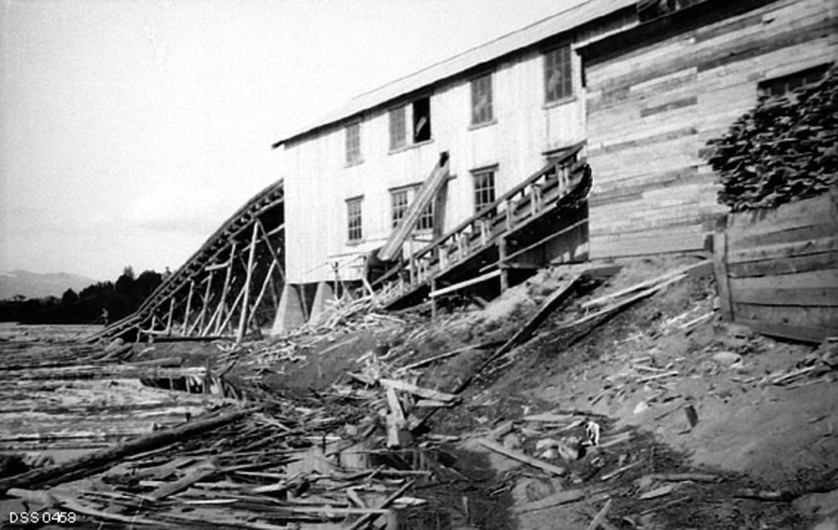 Moastøa sagbruk og høvleri i Målselv i Troms.  Fotografiet er tatt fra strandsteinene ved Målselva, som var tilførselsåre for tømmer til bruket.  Vi ser  saghusets langvegg mot vassdraget.  Bygningen var oppført i bordkledd bindingsverk på pyramideformete pilarer av betong.  Den hadde store vinduer, som gav dagslysinnsig i produksjonslokalene.  Ved den ene gavlen (til venstre i dette bildet) var det bygd en kjerrat som tok tømmer fra vassdraget opp til saginnretningene i annet etasjeplan.  Kjerraten kvilte på kraftige bukker av rundtømmer.  Sentralt på den nevnte langveggen var det ei renne som var ført gjennom veggen i annen etasje og ut, muligens for kapp og annet avfall.  Vi skimter også et kjerratliknende skråplan langs denne veggen.  Til høyre i bildet ser vi et bordkledd skur, muligens for hunved, som kunne brukes som energivirke.  I 1915 rapporterte skogforvalteren i Troms følgende:  «Jeg har trodd, at øvre Maalselvens 6 vandsager fuldt ud skulde kunne dække behovet for skur.  Naar undtages staveskjæring, foregaar det deroppe ikke forædling til utførsel, kun til eget bruk, gaardsbruk.  Tilsynelatende er der dog mangel.  En utenbygds motorsag har nemlig de par siste vintre hat stadig arbeide deroppe.  Dette trods for den lange transport av oljen og kostbar leie.»  Han mente at sagbrukskapasiteten var for liten, men at det villle komme flere «motorsagbruk».  Det skjedde imidlertid ikke i den hastigheten skogforvalteren hadde forestilt seg.  I 1918 meldte han at «Mangelen paa sagbruk blir mer og mer følelig.  Det har vakt almindelig glede innen Målselven, at staten akter å anlegge sagbruk i dalen.»  Påfølgende høst ble arbeidet påbegynt.  I juni 1920 startet man bygginga av sjølve saghuset med sagmester Ole A. Pedersen fra Revel-saga i Mo som sakkyndig ekspert.  Arbeidet gikk i rykk og napp, for det tok tid å få de tunge maskinene som skulle settes inn i bygningen før veggene ble kledd med panel fram til sagtomta.  Monteringa av lokomobilen, som skulle gi kraft 