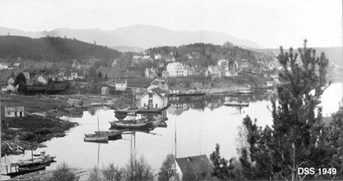 Strandstedet Leirvik på Stord i Hordaland.  Fotografiet er tatt fra et berg ned mot en stille fjordarm der det er ankret opp en del båter og skuter.  Vi ser et par store bryggehus.  Bakenfor ligger et tettsted med villaer, skole og forretninger.