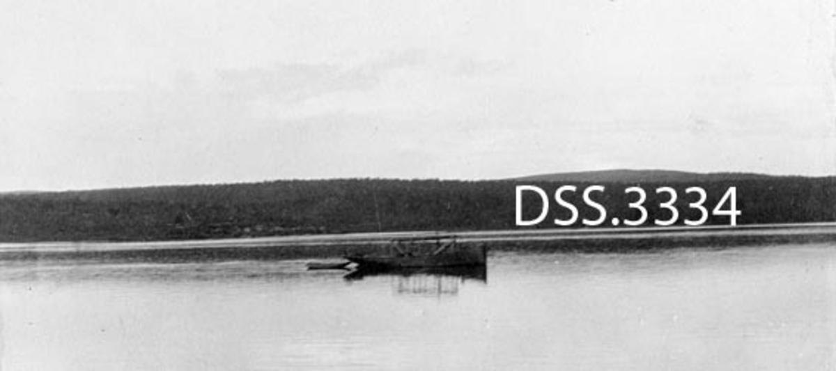 Motorvarpingspram på Vagatum i 1921.  Stile vatn uten tømmer.  Skogkledde bakkekammer i bakgrunnen.