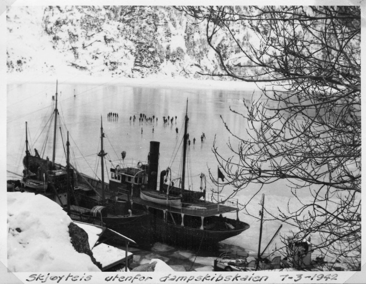 Lasteskip ved dampskips kaia, folk på skøyter, is på fjorden, vinter