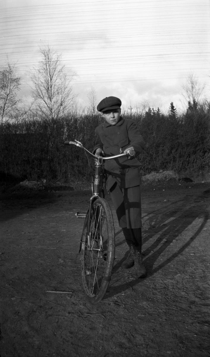 Ukjent gutt med sykkel på en vei.