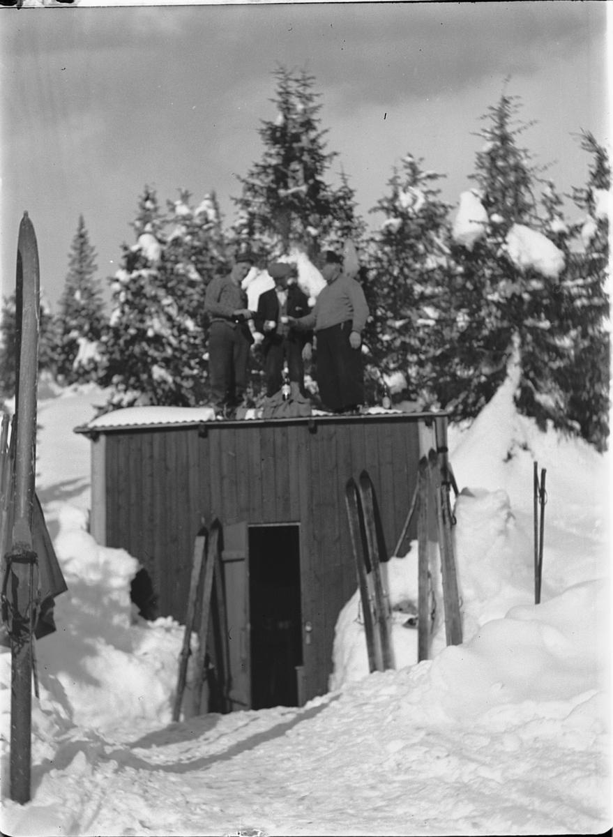 Tre menn på skitur tar seg litt drikke på taket av ei hytte.