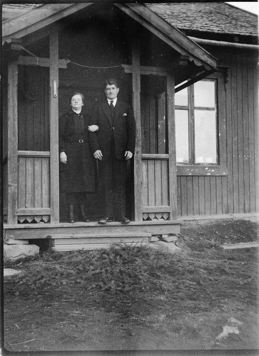 Ukjent kvinne og mann ved inngangsdør til hus.