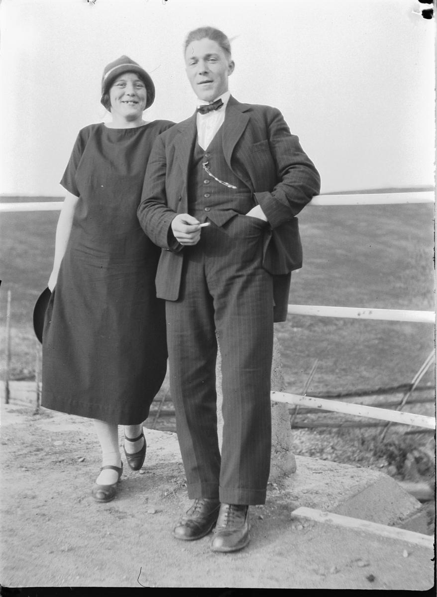 Ukjent kvinne og mann foran et rekkverk.