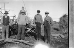 Gruppe menn ved en gammel skurtresker.