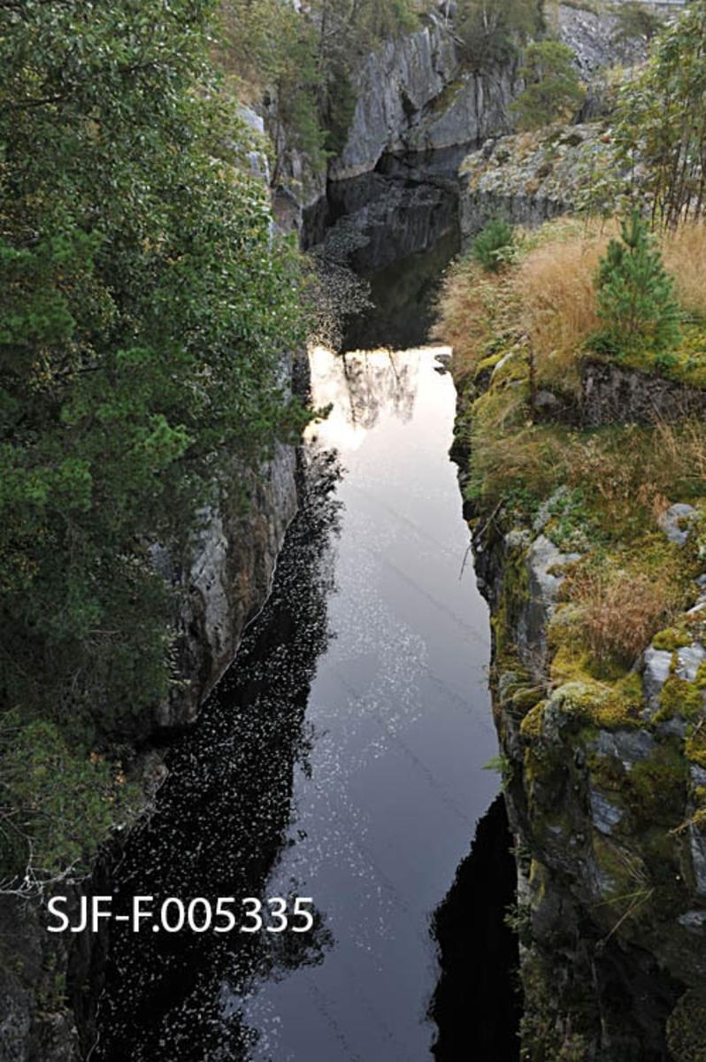 Satajuvet (i eldre tid også kalt «Satahullet») i Vallaråi i Seljord kommune i Telemark.  På strekningen mellom Flatsjå og Seljordsvatnet gjør dreier elva sørvestover¨i et fossefall ved garden Nordre Flatin, for deretter å dreie krapt sørøstover inn i et trangt juv like nedenfor.  Dette elvelandskapet skapte store problemer for fløtinga av tømmer fra Flatdal ned til Seljordsvatnet, og når fløtingsvirket satte seg fast i det djupe juvet, som var omgitt av steile bergflater, innebar det stor risiko å få det løst igjen.  Dette var en av årsakene til at myndighetene alt i 1858 tillot at det ble lagt ei spesiell avgift på 12 skilling per tylvt fløtingstømmerer her.  Midlene som kom inn fra denne avgiften skulle settes på en spesiell konto i Skiens sparebank.  Pengene som kom inn på denne måten skulle kommunestyret i Seljord disponere i henhold til en plan kanaldirektøren hadde fått utarbeidet for minering som skulle gjøre Vallaråi mer fløtbar.  Dette arbeidet pågikk i mange tiår, og sjøl om stadig flere hindringer ble sprengt vekk, hendte det at tømmeret satte seg fast her.  Dette fotografiet er fra den nedre, forholdsvis stilleflytende delen av juvet, tatt fra brua til gardene på vestsida av Vallaråi.  Den nevnte fossen like ovenfor ligger skjult bak bergnabben til høyre på bildet (jfr. SJF-F. 005336 - SJF-F. 005338)