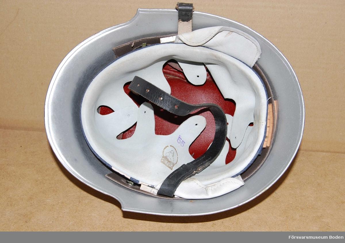 Av järnplåt, silverfärgad med klarlack. Lufthål på sidorna och framtill ett litet fyrkantigt hål för hjälmmärke. Insats i vitt skinn som justeras med snöre som passerar genom flikar, men snöret saknas. Under insatsen en rödfärgad skiva, troligen av värmeisolerande material. Hakrem av läder. Storlek 55, med kork- och träkilar monterade i mellanrummet mellan insats och hjälm.