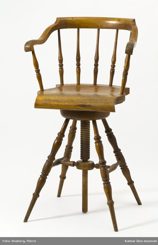 KLM 45007. Stol, skrivstol. Vridbar med träskruv, ryggstöd med sju stycken intappade, svarvade ryggpinnar. Rundat armstöd och ryggöverstycke utformat i ett stycke. Fyra stycken utåtställda svarvade ben med tvärslå och sidoslåar.