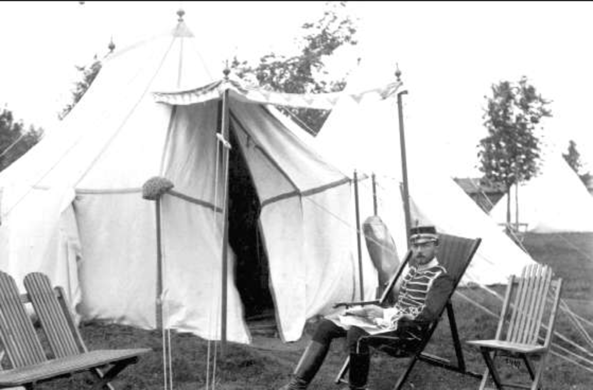 """Prins Eugen framför sitt tält på Sanna Hed. OBS, mankskyddet (""""padden"""") på tork på vänstra stolpen. OBS, bild och kartong hör sannolikt inte ihop. Franske fotografen J.David fotograferade troligen ej på Sannahed."""