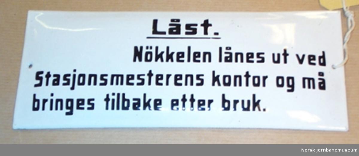 """Skilt : """"Låst! Nøkkelen lånes ut ved Stasjonsmesterens kontor og må bringes tilbake etter bruk."""" - fra jernbanestasjon"""