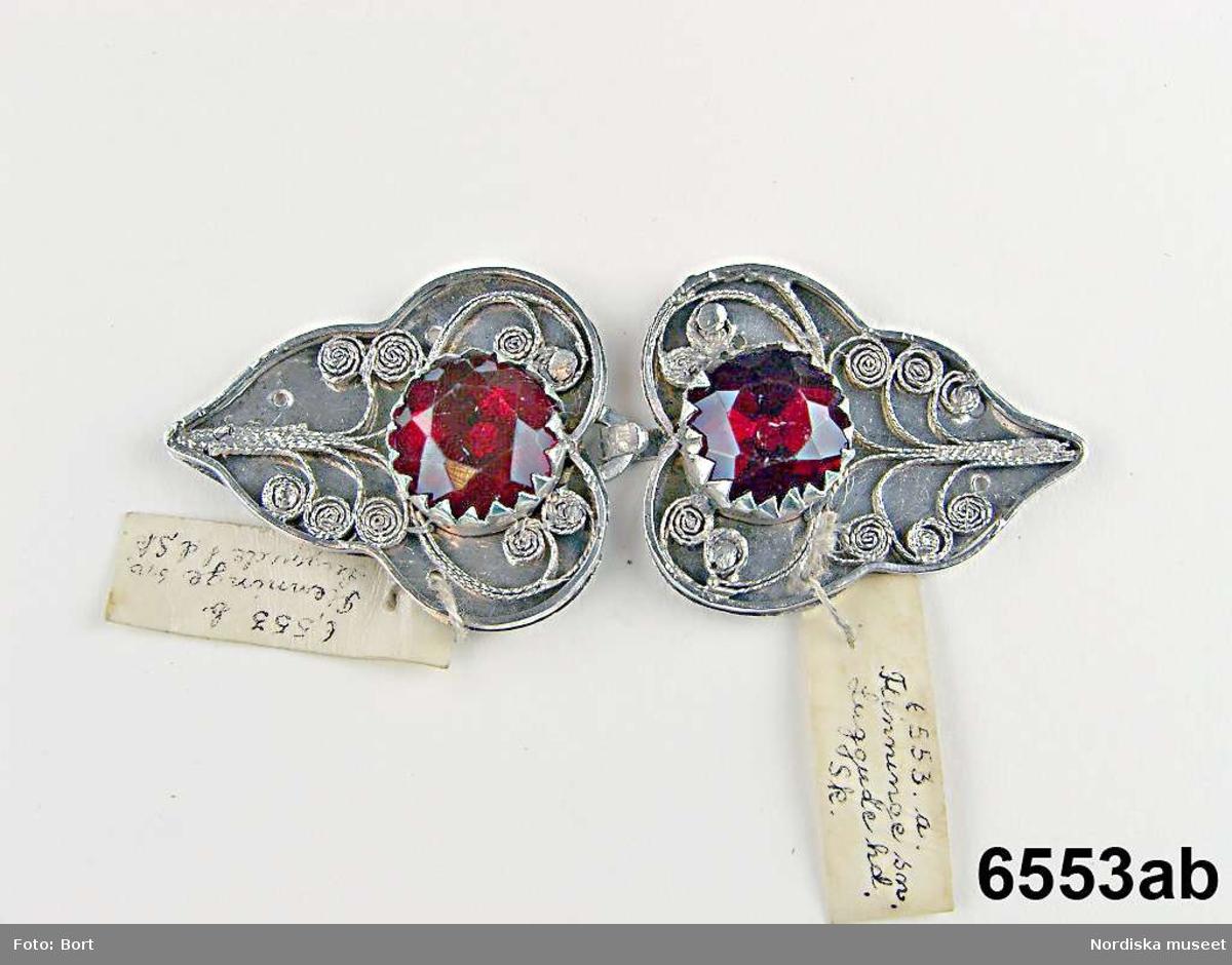 """Huvudliggaren (år 1875): """"6.553 Bröstspänne fr. Fleninge sn, Luggude hd. Skåne. Ss. 6,534 [= Gm. fröken Ingeborg Tauström i Helsingborg. Ank. i början af år 1875].""""  a-b) Spänne, bestående av två svagt hjärtformiga, snarast bladformiga silverplattor. I var platta fyra hål att sy fast spännet i. Pålött filigranornament med sarg mot förgylld bakgrund. På varje spännhalva en stor, rund, röd fasettslipad glassten i klofattning. Spännet knäppes med hake och hyska. På både hakdel (a) och hyskdel (b) mästarstämpel IM slagen två gånger, Jöns Petter Möller, verksam i Helsingborg 1807-1831. /Marie Tornehave 2008-12-08"""