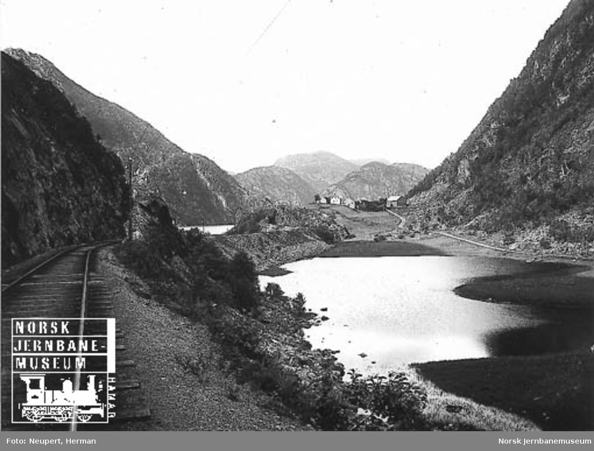 """Vossebanen sett østover mot Dalseid med Bolstadfjorden i bakgrunnen og """"Litlesjøen"""" til høyre"""
