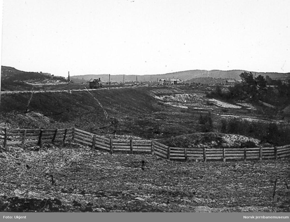 """Damplokomotiv på """"Bredtvedt Bank""""; den svære fyllingen som i 1861 erstattet en trebru. Grorud stasjon i bakgrunnen."""