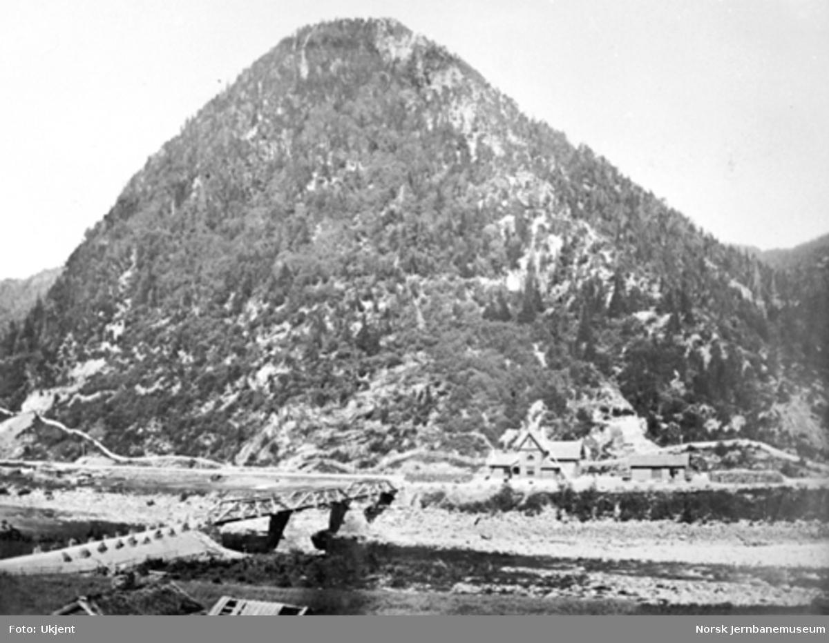 """Rognes stasjon sett fra den andre siden av elva med åsen Rødsten (""""Sukkertoppen"""") i bakgrunnen"""