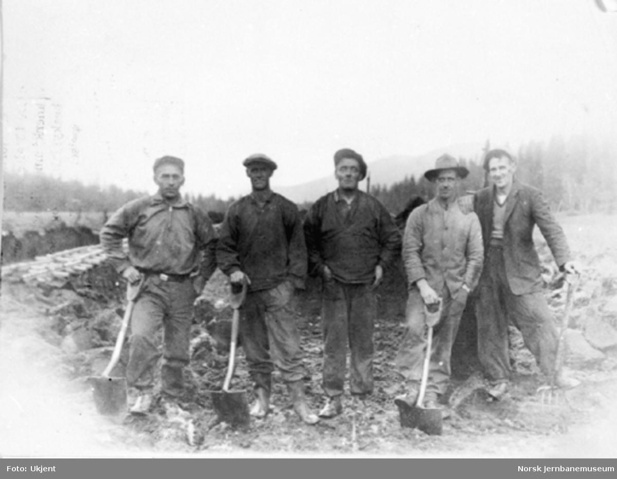 Gruppebilde av fem anleggsarbeidere med spader og greip