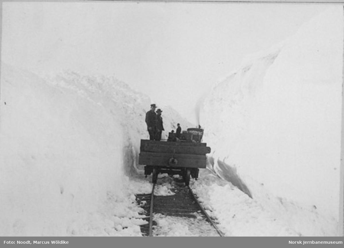 Tog mellom høye brøytekanter på Arvedalslinjen (Kongens Grubes bane) pæl 600, sett i retning gruven