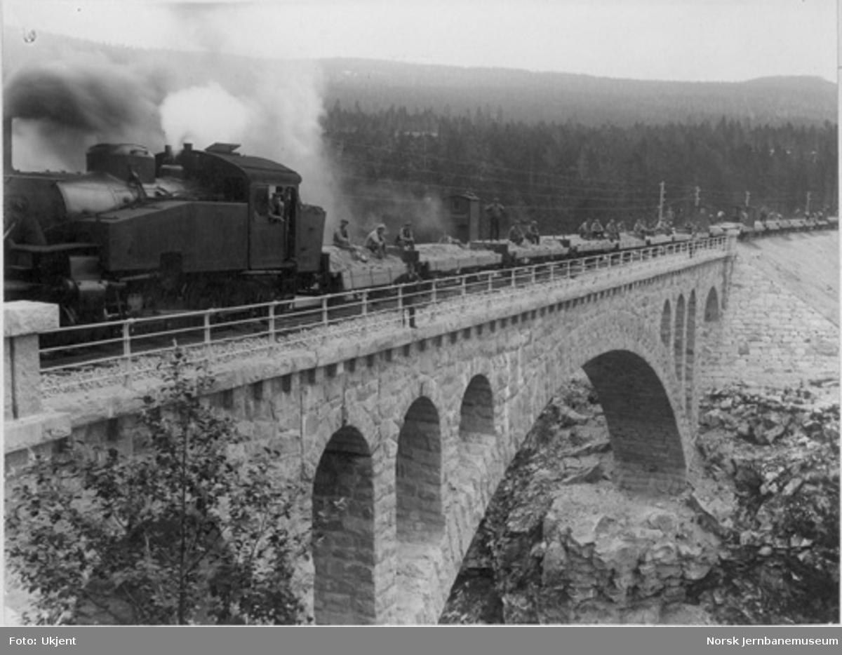 Grustog på Jora bru med damplokomotiv type 34a nr. 345 og anleggsarbeidere på grusvognene