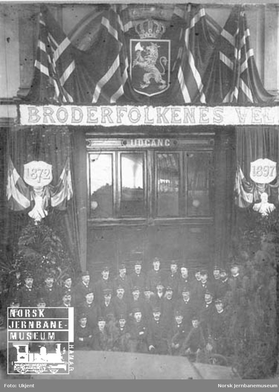 """Gruppebilde av jernbanepersonell under dekorasjon med """"Broderfolkenes vel"""" og årstallene 1872 og 1897 : Kong Oscar IIs 25 års jubileum som konge"""