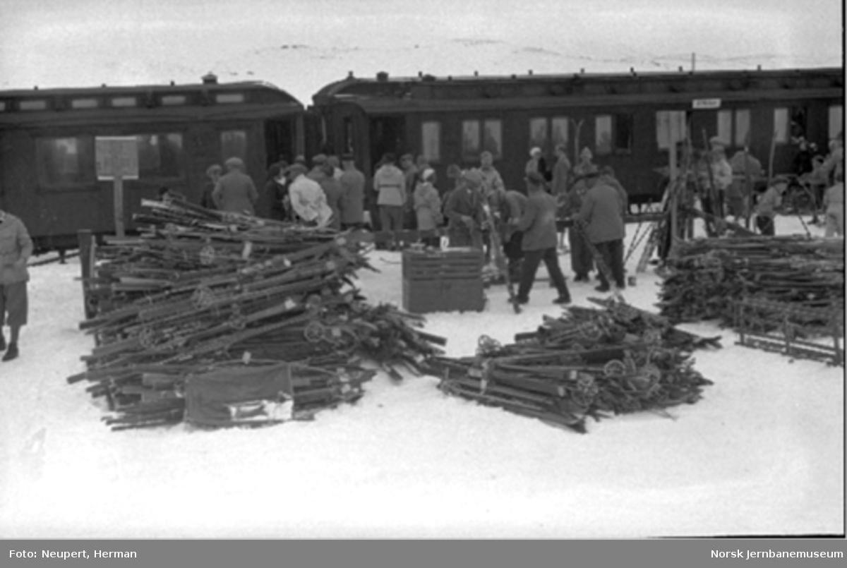 Ustaoset stasjon med stabler av ski og mange reisende foran Bergenstoget