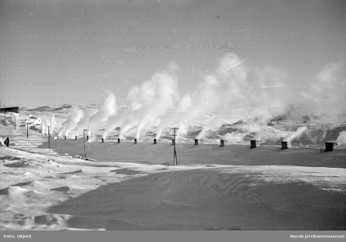 Røyk fra passerende tog siver ut av snøoverbygg