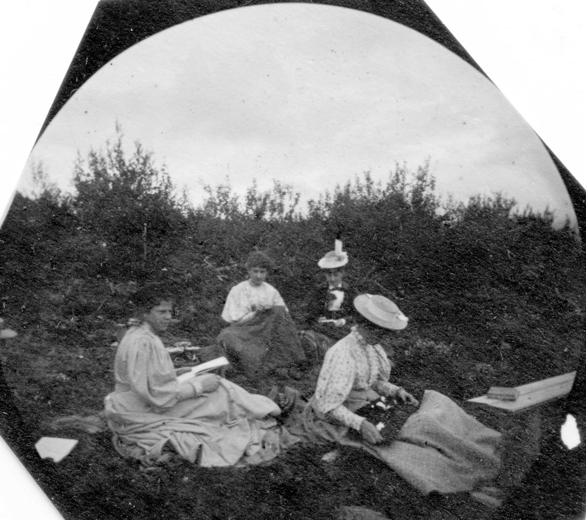 Fire damer sitter på bakken i skogen med tegnesaker.