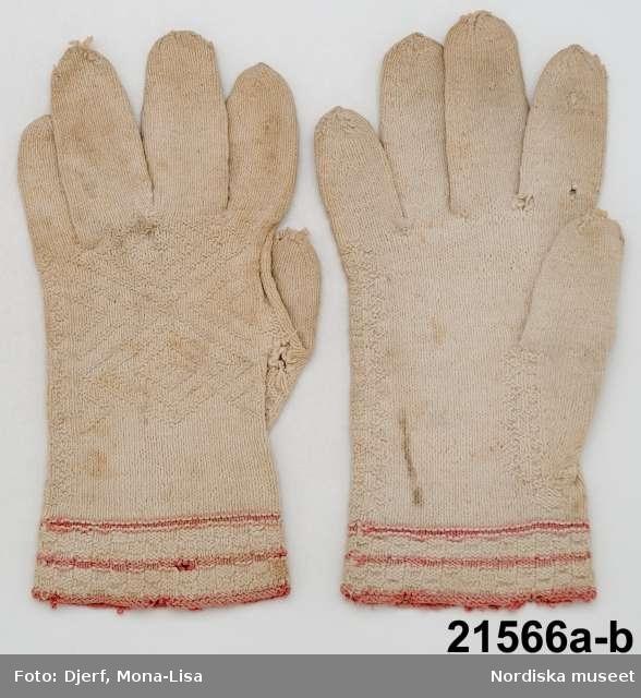 1 par fingervantar för man stickade av vitt bomullsgarn, slätstickade med  krage i rutstickning med växlande räta och aviga maskor och med 3 rosa smala ränder. På handens ovansida mönsterstickning med romber i aviga maskor, även mönster kring tummen. Sådana bomullsvantar stickades på vissa orter och försåldes av gårdfarihandlare. /Berit Eldvik 2013-03-12