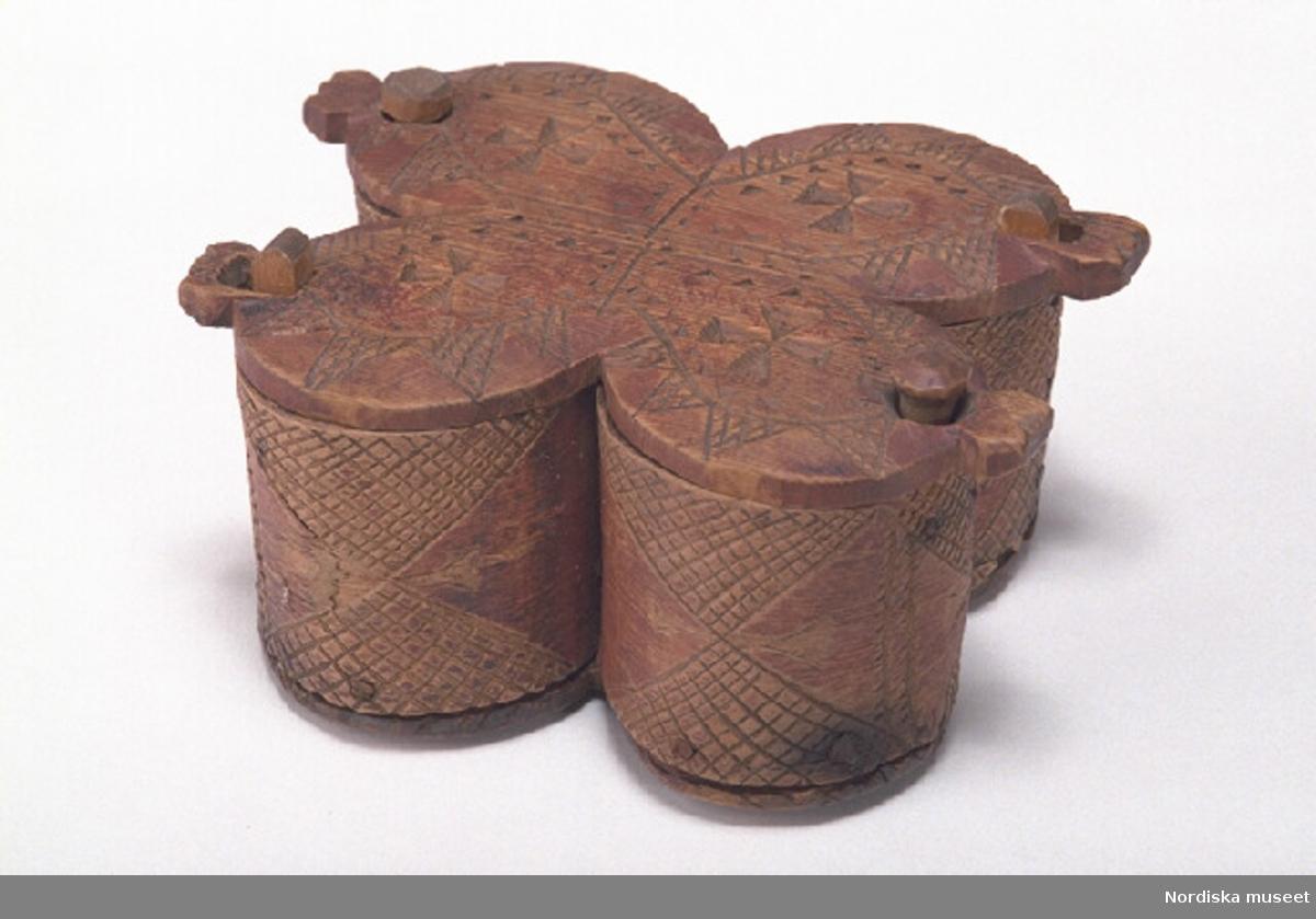 """Inventering Sesam 1997-1998: L 13, B 11, H 7 cm Kryddlåda, svepäska, två 8-formiga svep, sammanlagt fyra fack med gemensam botten. Lock och botten av barrträ, svep av lövträ, med fals. Svepen fästade med snett islagna islagna dymlingar av trä samt någon enstaka järnspik. Hopfästning av svepen med rottågor, samtidigt fastsydda i varandra. Utskurna ståndare av lövträ, två fjädrande och överkragande, fästade på svepens insidor med skruvar, genomgående vid botten. Två vridbara knäpplock, svagt fasade kanter. Svep och lock med skuren, rätlinjig dekor i rutor, uddsnitt samt på locken även kilformiga kors. Målad i rött, färgen till stor del avskavd. På bottens undersida inskuret """" K P D  1735 """", svagt fasad kant. Agnetha Blomberg 1997"""