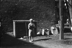 Barn i Gråbeingård, Oslo, 1925. Gutt ved søppelkasser med ka