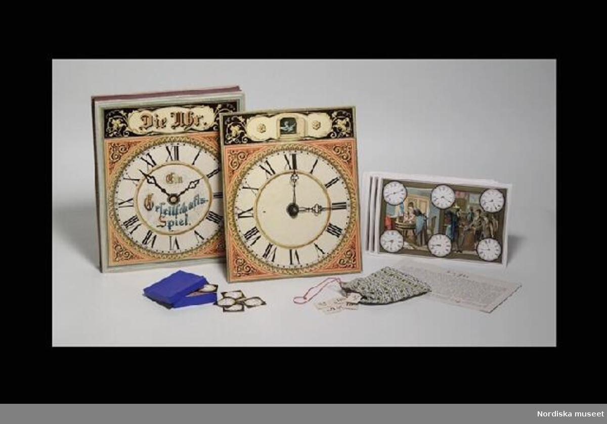 """Huvudliggaren: """" 'Die Uhr, Ein Gesellschafts Spiel'; urtavla, papp, 2 rörliga visare, påse med dragsko med papplappar med klockslag; blå ask med papplappar med urtavlor; 12 färglitos med 6 urtavlor å varje, husliga scener m.m.; spelreglor på tyska; ask papp, trycklock med litogr. urtavla; Sign J S No 18.""""  Inventering Sesam 1996-1999: Kartong L 32,5 cm, B 27 cm, H 4,5 cm Spel i originalförpackning, pedagogiskt spel om att lära sig klockan. Spelet bestående av: Urtavla av tjock papp med flerfärgstryck visande urtavla med romerska siffror och dekor i orange och svart, rörlig tim- och minutvisare av metall. På baksidan stöd av papp och kugghjul till visarna.  12 st rektangulära pappskivor med flerfärgstryck visande männniskor i olika vardagliga situationer och 6 st vita urtavlor med olika klockslag. 25 x 16 cm. Pappask klädd med blått papper. I asken 49 st små papplappar visande urtavlor med olika klockslag. Ask 8,3 x 8,3 x 2 cm. Lappar 3,7 x 3,7 cm. Tygpåse med röd tråd till dragsko, påsen mönstrad i grönt och blått mot vit botten. I påsen 72 st små papplappar med svart tryck visande olika tider, t ex """"10,19"""", """"6,42"""" osv. Påse  14 x 12 cm, Lappar 2,7 x 2,7 cm. Papper med spelregler, på tyska, tryck på bägge sidor. Rubrik """"Spiel=Regel / No 18"""". 14 x 24 cm. Allt ligger i orignalkartong med lock. Kartongen vit med blå undersida, Trästav klistrad i botten. Locket med flerfärgstryck visande urtavla (samma som som ovan) och text """"Die Uhr. / Ein Gesellschaft-Speil."""" och litet firmamärke under """"J S"""" inskrivet i kavelliknande form och """"No 18"""". Leif Wallin nov 1997"""
