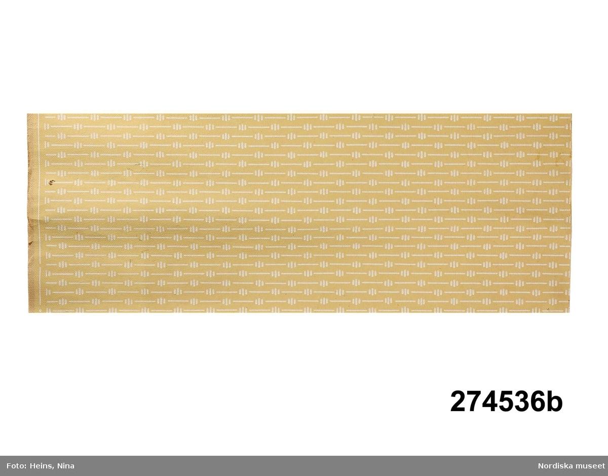 """Huvudliggaren: """"a-c Tapetprov, papper, tryckt mönster; a/ äldre, ljusbrun med breda ränder, finmönstrade i orange och guld; b/ tapet före den nuvarande, gul botten, strecktecknat regelbundet mönster i vitt; c/ tapet i bruk från 1968, pressad yta med effekt av grov väv samt bård till i guld, beige och ljusbrunt, randig.""""  Katalogkort: """" a) äldre tapet. Ljusbrunt papper med breda ränder som är finmönstrade i orangerött och guld. b) tapet före den nuvarande. Gul botten med streck-tecknat regelbundet mönster i vitt. c:1) tapet i bruk 1968. Pressad yta med effekter av grov väv. c:2) gul bård till föreg randig i guld, beige och ljusbrunt. Dessa tapeter har använts i giv:s sommar hem vid Ryssgård, (största norra rummet; C:1 och C:2 i båda rummen mot norr). Hon flyttade dit 1936. Se uppteckningar K.U. 2162. E.Hk. (=Elisabet Hidemark).""""  a) Består av två delar. Handskrift på baksidan av tapeten.  Anm (den större delen): Kant nagg, revor, veck. Anm: (den mindre delen): Revor, veck. b) Handskrift på baksidan av tapeten. Anm: Mindre revor. /Cecilia Wallquist 2006-10-24."""