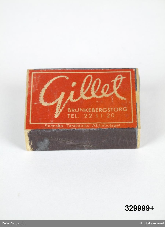 """Tändsticksask av papp och trä, med instickslåda. Plån på långsidorna. Blå, på ena sidan etikett med reklamtryck i form av vit text på röd botten """"Gillet / BRUNKEBERGSTORG /TEL 22 11 20 / SVENSKA TÄNDSTICKS AKTIEBOLAGET"""". Asken är tom.  Reklamtexten syftar på hotell och restaurang Gillet som låg på Brunkebergstorg i Stockholm.  Under 1900-talet användes ofta reklam på  tändsticksaskar/tändsticksplån i marknadsföringen av olika varor och tjänster. Askarna/plånen delades ofta ut gratis och många restauranger lät dem ligga framme på borden för gästerna. Under slutet av 1900-talet blir detta mindre populärt, delvis för att tändaren blir vanligare, men framför allt beroende på att färre rökte och att rökning inte längre förknippades med något positivt. Tändsticksasken ingick i en större samling som ihopsamlats av givarna under sina bilresor under 1950-talet och fram till 1980-talet inom och utom Sverige. Ett urval ur samlingen förvärvades av Nordiska museet 2009. /Leif Wallin 2009-09-30"""