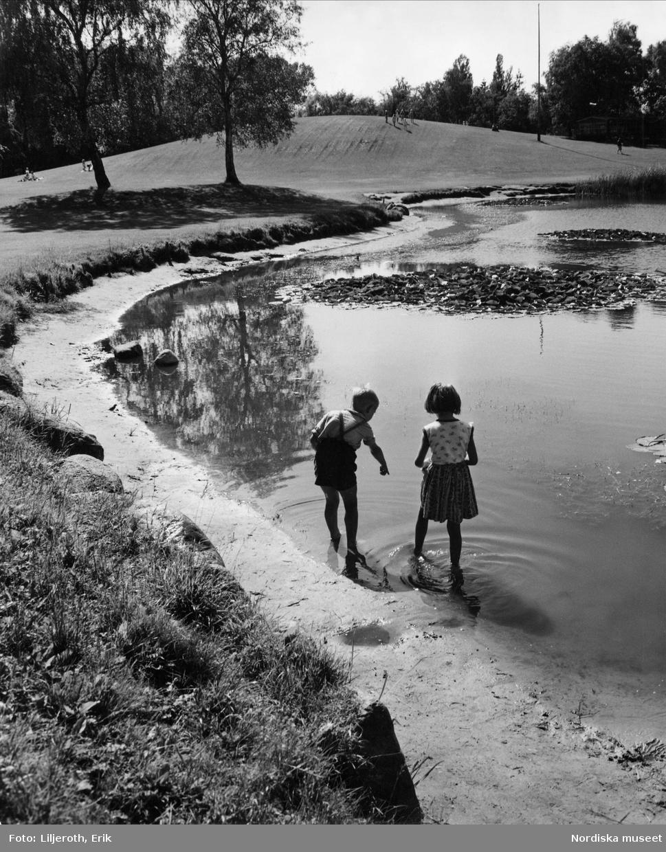 Två barn en pojke och en flicka som leker vid en damm i en av Malmös parker, troligen Beijers park.
