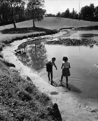 Två barn en pojke och en flicka som leker vid en damm i en a