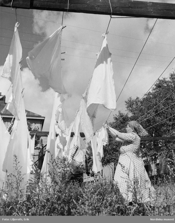 Göteborg. Kvinna hänger upp tvätt utomhus.