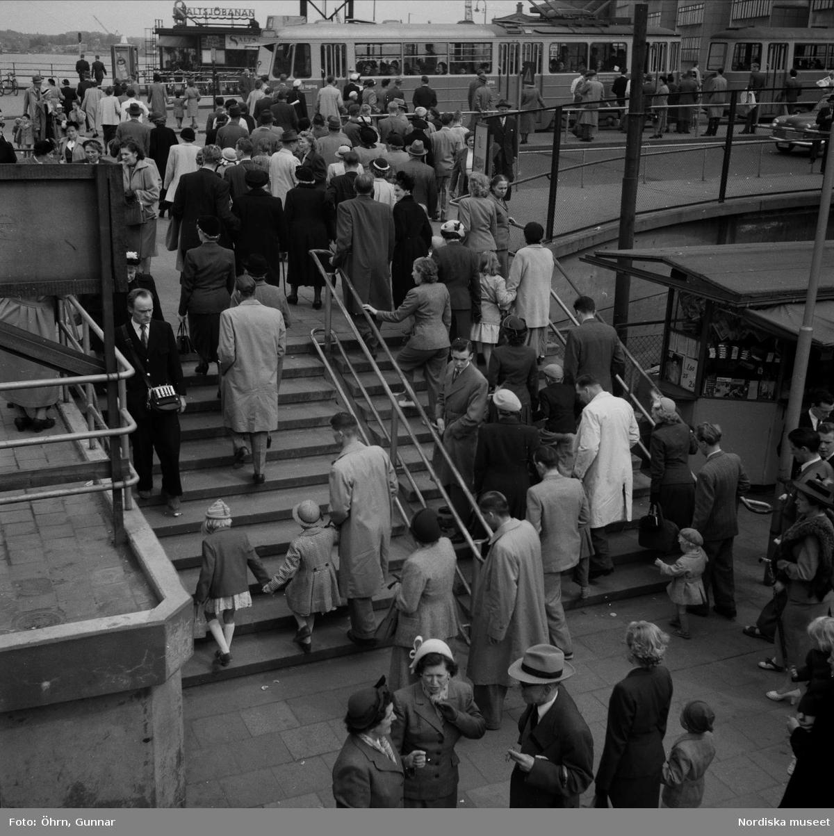 Rusningstid vid Slussen, Södermalmstorg. Människor i trappa, spårvagn i bakgrunden.
