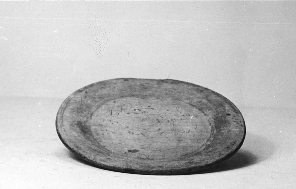 Tallrik av trä. På brättets undersida inskuret: XII.