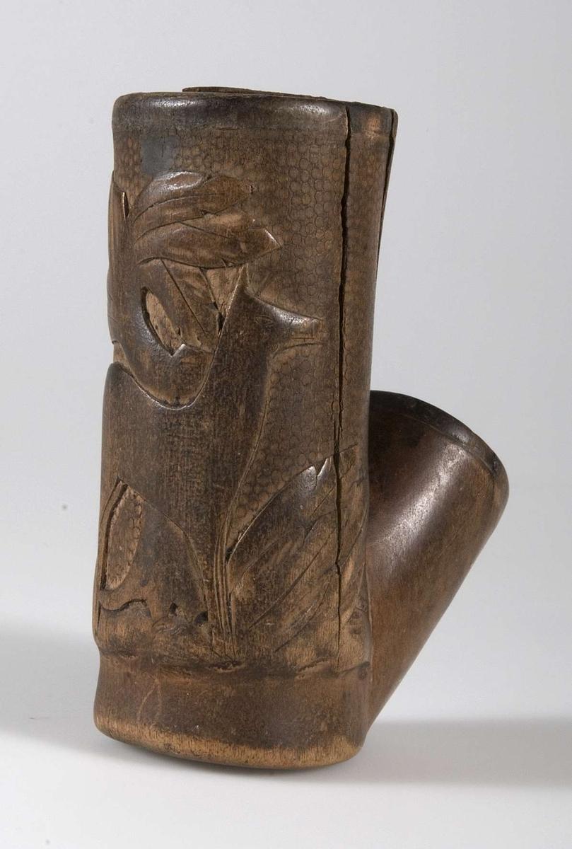 Piphuvud av trä. Skulpterad relief, föreställande en hjorthind och växter. I piphålet en järnring.