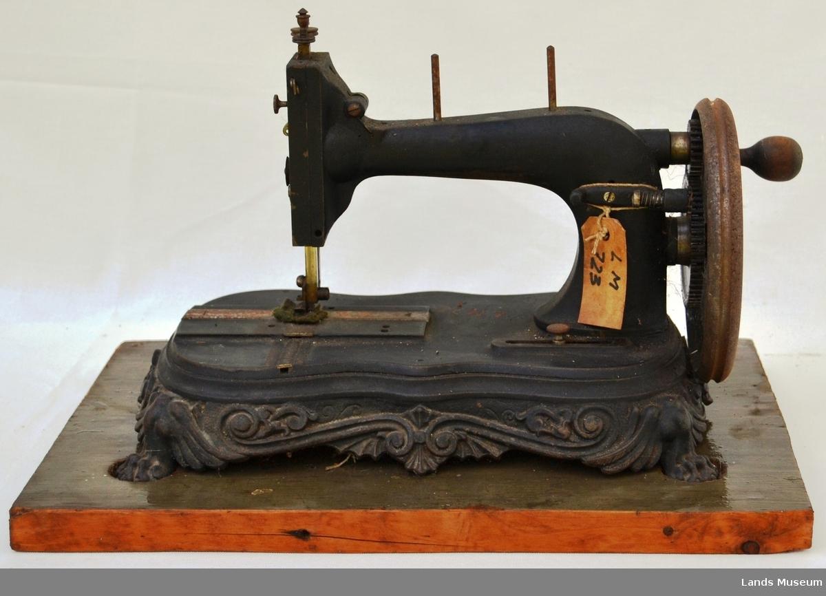 """Handdreven symaskin montert på treplate. Fot i støpjern med løveføtter og """"utskjæringer""""."""