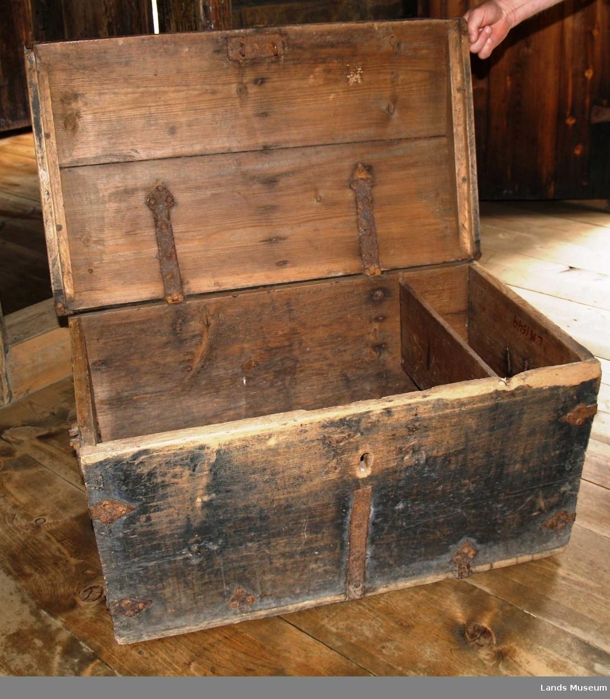 Solide jernbeslag, malingen avslitt på lokket, to hanker til å flytte den med, buet lokk, leddik på ene kantsiden.