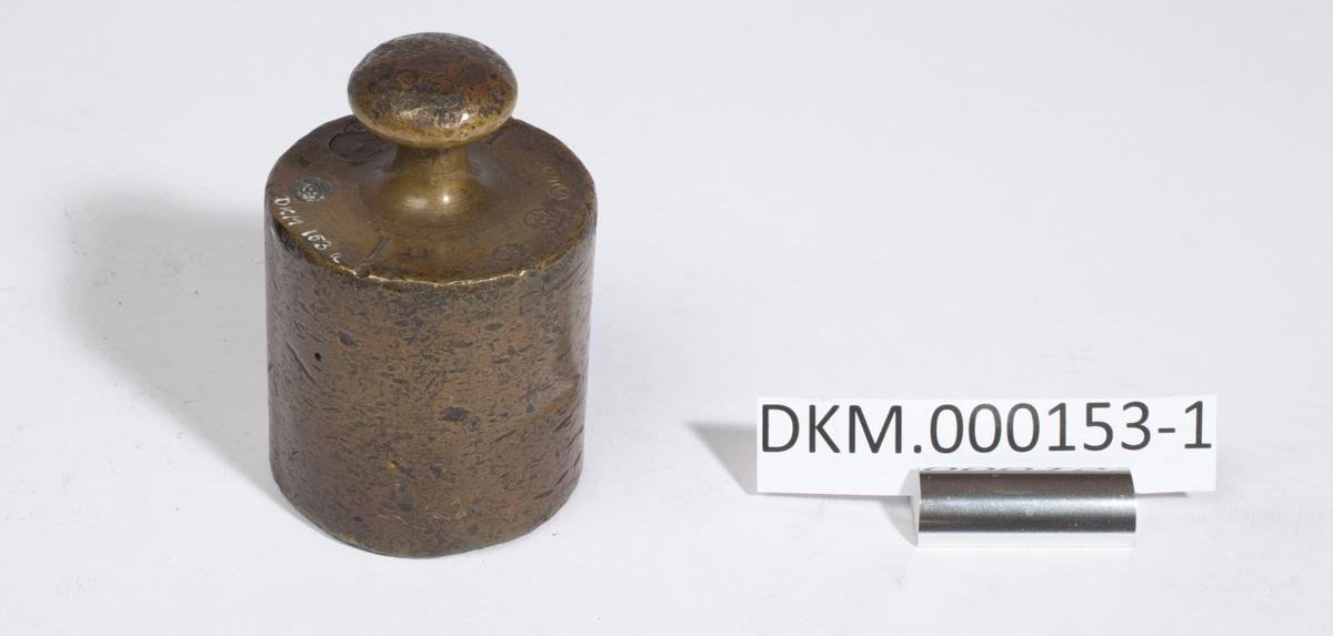 Sylinderformet lodd med håndtak. Kontrollstempel i loddet.