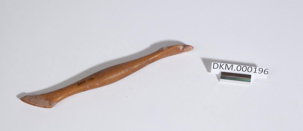 Rund trepinne med spiss i den ene enden. Den smalner noe etter begge endene og blir tykkere igjen på midten.