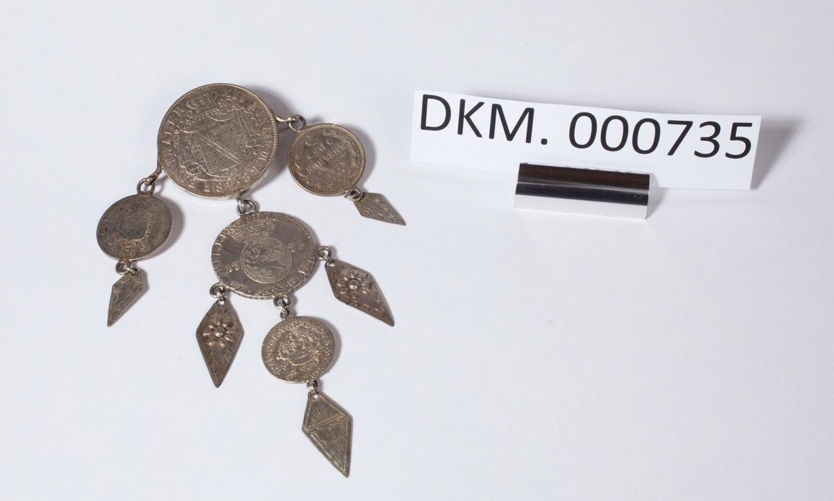Smykke med nål bestående av fem sølvmynter og og fem mindre sølvplater som er tilnærmet rombeformet. De ti delene er montert sammen med små ringer og danner tilsammen ett trekantformet smykke.