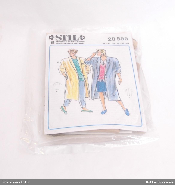 Mønsteret og forsiden er pakket inn i en blank plastikkpose Strektegningen på forsiden forestiller to kvinner med frakk, en som en kan sy av mønsteret. En vid frakk som går til under kneet.