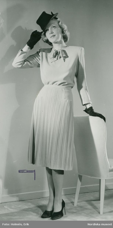 Helporträtt av kvinna i knytblus och kjol, samt hatt och handskar.