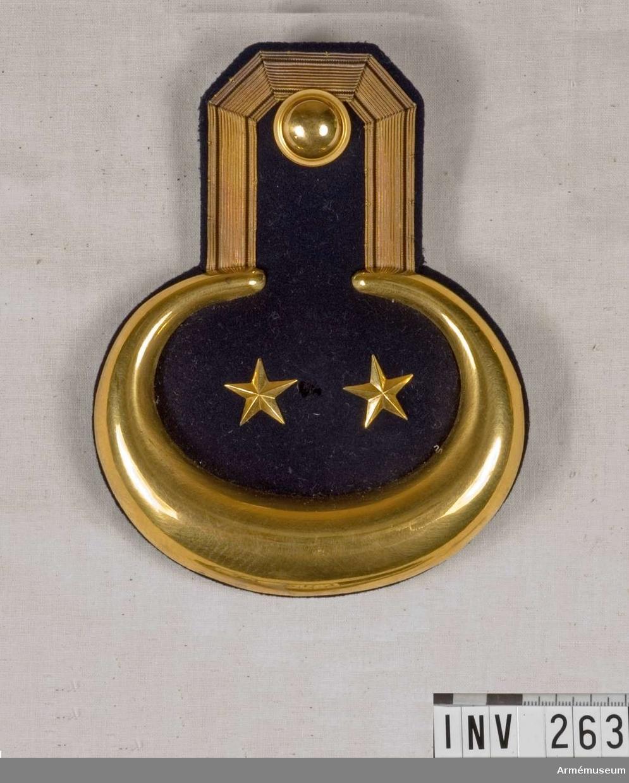 Epåletten har mörkblå klädesmatta och foder. Guldgalon 15 mm bred runt övre delen, och en förgylld mässingsplåt kring delen. Två förgyllda stjärnor betecknande löjtnant och regementets knapp av m/1779. På fodersidan finns en hake 35 mm lång att fästa epåletten vid vapenrocken med. Haken bär en stämpel med: M.E.A. Militärekiperingsaktiebolag. Fyllning eller stoppning med blånor. Rulla 1883.